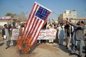 Muslims in Pakistan burning an America flag over drone strikes  stock photo