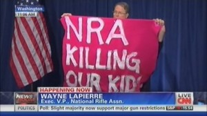 A protester from Code Pink interrupts a press conference following the Sandy Hook shooting, photo screenshot CNN coverage