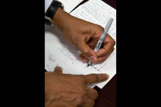 President Barack Obama signs letters written by Hinna Zeejah, Grant Fritz, Julia Stokes, and Teja Goode backstage in the Eisenhower Executive Office Building's South Court Auditorium after unveiling new gun control proposals as part of the Administration's response to the Newtown, Conn., shootings, and other tragedies, Jan. 16, 2013. The children wrote to President Obama in the wake of the Newtown tragedy expressing their concerns about gun violence and school safety. (Official White House Photo by Pete Souza)