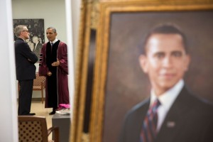 President Barack Obama is reflected in a mirror as he talks with Chief of Staff Denis McDonough prior to participating in the commencement ceremony at Morehouse College in Atlanta, Ga., May 19, 2013. A painting of the President stands in the foreground. (Official White House Photo by Pete Souza)