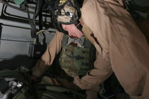 As they fly towards a hospital in Iraq, Lt. j. g. Paul Greer, a chaplain with 2nd Marine Aircraft Wing, prays for a wounded Soldier during an urgent casualty evacuation mission, Oct. 27. The Soldiers condition improved as Greer prayed over him. photo/ 2004 USMC