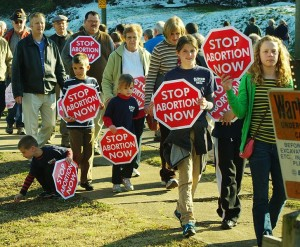 "Participants in the ""March for life"" walk along Concord Avenue in Knoxville, Tennessee, United States. The march is held annually to mark the anniversary (January 22) of the U.S. Supreme Court decision, Roe v. Wade. The signs, designed to resemble stop signs, read, ""Stop abortion now."" photo Michael Stansberry via wikimedia commons"