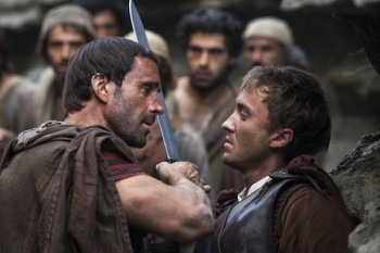Clavius (Joseph Fiennes, left) warns Lucius (Tom Felton) to let them all pass, after he discovers him leading the apostles away from the Roman soldiers in TriStar Pictures' RISEN.