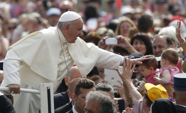 Pope Francis greets a baby as he arrives to lead his general audience in St. Peter's Square at the Vatican May 20. (CNS photo/Paul Haring) May 20, 2015.  photo courtesy of USCCB