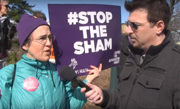 Pro choice abortion supporter at rally with Stop the Sham sign