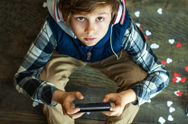 Fashionable teenager boy in headphones and with a mobile phone playing an Internet game. The dependence of children from online games. Internet addiction