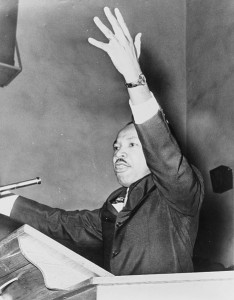 1962 New York World-Telegram and the Sun staff photographer Martin Luther King, Jr., half-length portrait, facing left, with left arm raised, at freedom rally, Washington Temple Church / World Telegram & Sun photo by O. Fernandez.