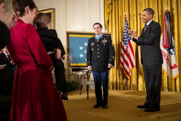 President Barack Obama applauds as Staff Sergeant Clinton Romesha looks over at his wife and children after receiving the Medal of Honor during the award ceremony in the East Room of the White House, Feb. 11, 2013. (Official White House Photo by Pete Souza)