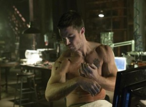 Stephen Amell as Oliver Queen stitching up his injuries