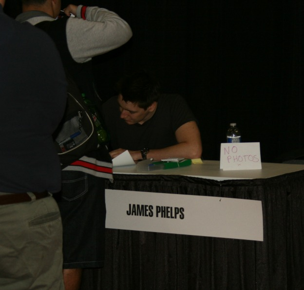 "James Phelps signs for a fan as the small ""No Photo"" sign serves as a reminder to those in the area to follow the MegaCon order to meet and greet the guests."