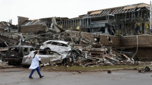 A nurse walks past the devastation, what is left of the Moore Hospital
