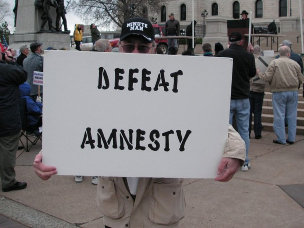 man with defeat amnesty immigration sign