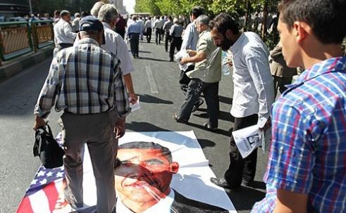 Protests in Iran involve spitting on photos of President Obama
