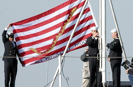 Sailors aboard the aircraft carrier USS Kitty Hawk (CV-63) raise the First Navy Jack (Don't Tread on Me), Yokosuka, Japan (Dec. 23, 2001). US Navy Photo by Photographer's Mate 2nd Class David A. Levy