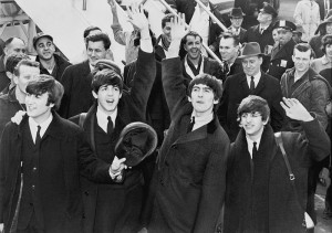 The Beatles wave to fans after arriving at Kennedy Airport on February 7, 1964