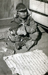 A child beggar in the streets of Beijing: the paper in front of him tells a story of his plight 1934 photo by Ellen Catleen public domain