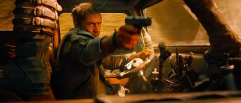 Tom Hardy Mad Max Fury Road takes aim with gun