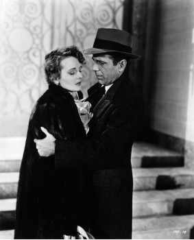 "Mary Astor as Bridgid O'Shaughnessy/Miss. Wonderly/Miss. LaBlanc and Humphrey Bogart as Sam Spade, who wears hat/fedora in ""The Maltese Falcon"""